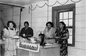 Members of the Fort Peck Friendly Homemakers Club prepare to serve food at a fund-raiser for a children's Christmas party, circa 1948. Early clubs on the Fort Peck Indian Reservation were segregated by race, but the Extension Office worked to integrate clubs in the 1960s.