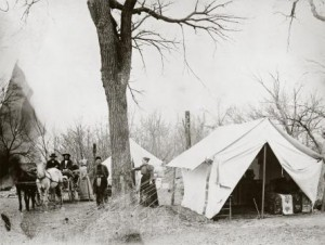 One of the first two women to serve as an allotment agent. Clarke is shown here standing next to the wagon. at the Otoe Agency in Oklahoma, circa 1891. The beautiful quilt on her bed hints at her effort to make camp life comfortable. MHS PHoto Archives 941-747