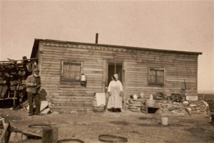 An African American homestead couple stand in front of their home.