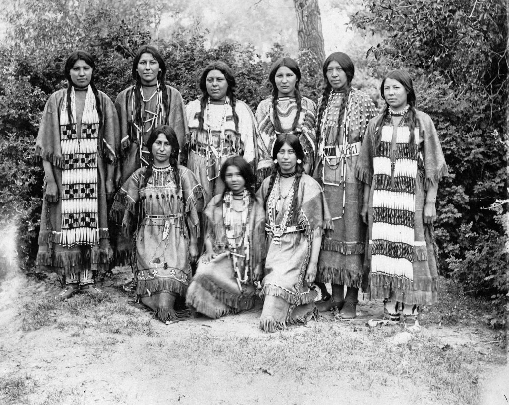 """Over the course of five months, more than three million fair-goers gaped at Indian students demonstrating their skills in domestic and industrial arts, drama, and music. However, the almost all-white audience devoted most of its fascination to ten Indian girls playing basketball and, between games, reciting Longfellow's """"Hiawatha"""" in distinctive buckskin dresses. Standing (from left) are Nettie Wirth, Genevieve Healy, Josephine Langley, Belle Johnson, Minnie Burton, Sarah Mitchell, and kneeling (from left) are Emma Sansaver, Gertrude LaRance, and Rose LaRose."""