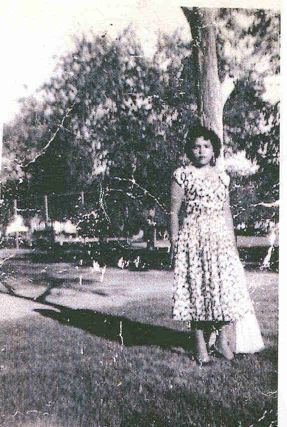 A young Lula Martinez, poses by a tree in a patterned dress.