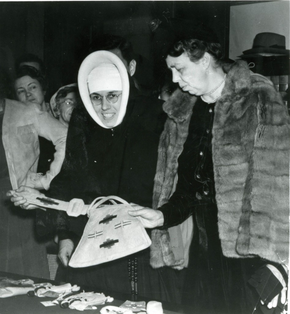 Sister Providencia, in full habit, with Eleanor Roosevelt, in a fur cape, admiring a decorated bag.