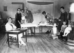 A makeshift doctor's office--probably in a school. A woman sits at a table (left.) Back left a female nurse holds a toddler while a male  doctor listens to his lungs with a stethoscope. Another woman holds a baby flat on a table, while a third woman  weights and measures a 3-4 year old on a doctor's scale. Two children sit in a rocking chair waiting.
