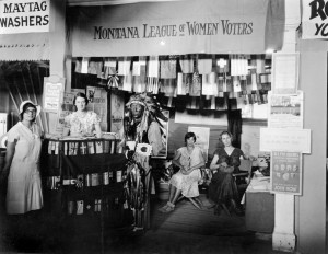 Montana League of Women Voters booth, decorated with flags of all nations . An Indian man in a ceremonial headdress stands at the counter, staffed by two young women. Two other women sit in the background.