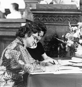 Louise Cross, sitting at a table in the capitol, signing the constitution. Next to her is a woman pointing at where to sign.