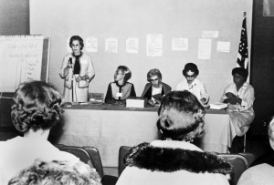 A woman speaks into a microphone. Four other panel members (all well-coifed women) sit at a head table facing the audience.