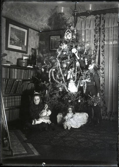 A girl hangs an ornament on a Christmas tree, and another girl poses in front of the tree holding a doll. On the left side of the photograph, four shelves of books can be seen and a painting above on the wall. Flooring is wood and two rugs are visible on the floor.